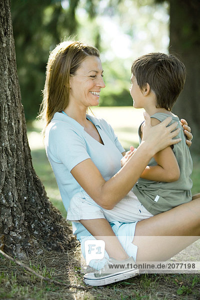 Mother and son outdoors  boy sitting on woman's lap