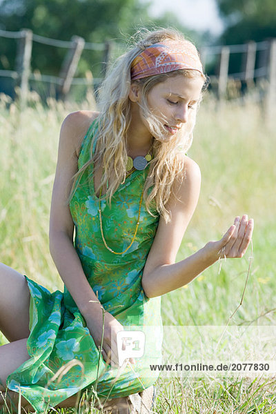 Junge Frau im Sommerkleid im Feld hocken  Blick auf Zweig von Gras