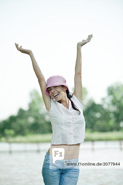 Frau stehend mit Arme  zeigt nackten Zwerchfell  Lächeln in die Kamera