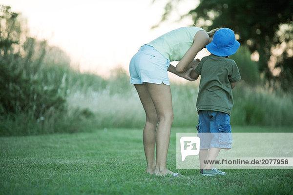 Mutter und Sohn stehend auf Rasen  Frau Boy zu sprechen über biegen