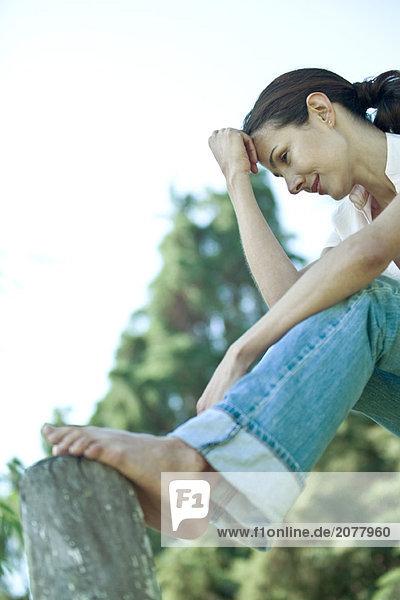 Frau sitzen im Freien mit Füßen auf hölzernen post  Untersicht