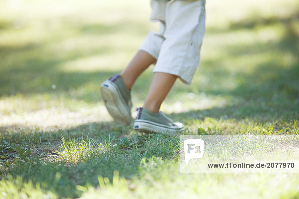 Boy gehen über Gras  niedrige Abschnitt