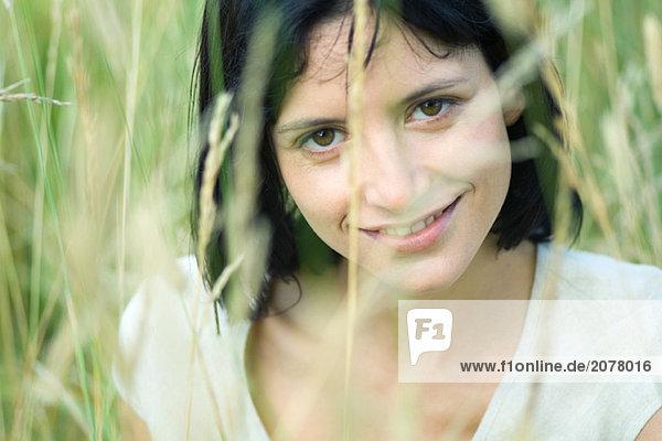 Frau Lächeln in die Kamera  verschwommen Vegetation im Vordergrund  Kopf und Schultern