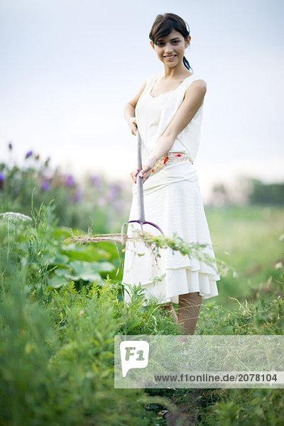 Junge Frau Entfernen von Unkraut im Garten  volle Länge  Lächeln in die Kamera