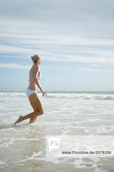 Junge Frau im Bikini  ausgeführt in surf