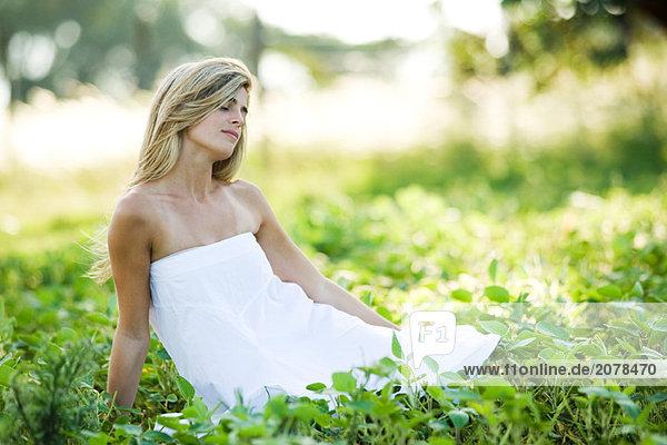 Junge Frau tragen Kleid  sitzen im Feld