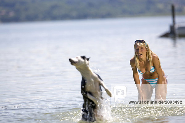 Young woman playing with dog in lake