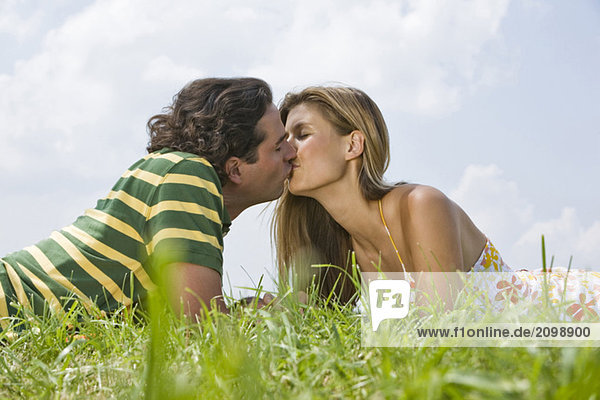 Couple lying in meadow  kissing
