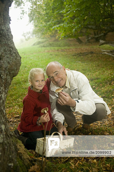 Germany  Baden-Württemberg  Swabian mountains  Grandfather and granddaughter searching mushrooms in the forest  portrait