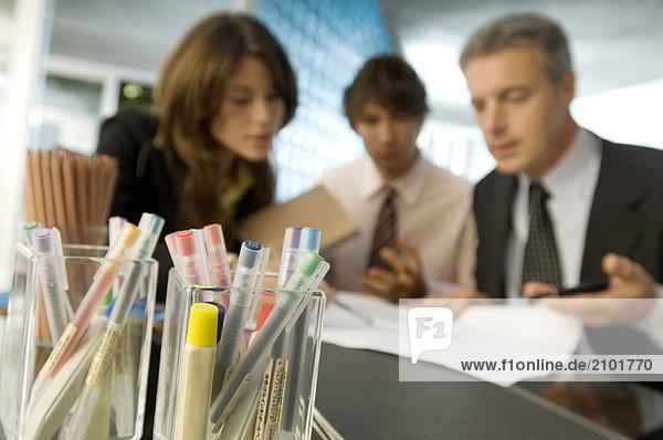 Farbstift mit Geschäftsleuten im Hintergrund