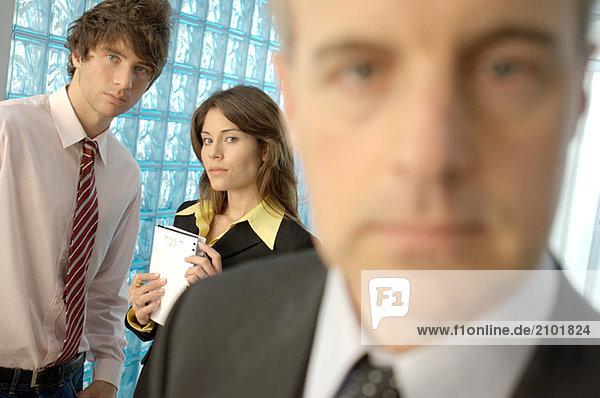Kaufmann im Büro mit Kollegen im Hintergrund