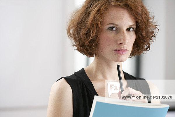 Junge Frau blickt nachdenklich in die Kamera  fully_released