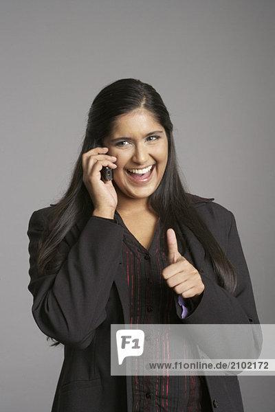 Geschäftsfrau telefoniert mit einem Handy zeigt Daumen nach oben  fully_released