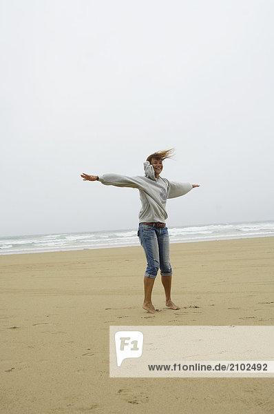 Frau dehnen ihren Armen am Strand