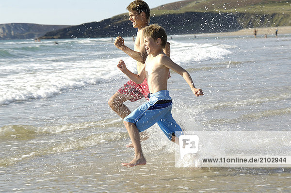 Side profile of two brothers running on beach