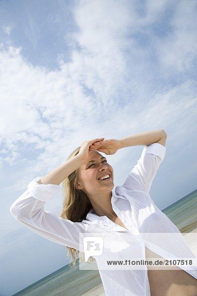 Frau im weißen Hemd am Strand