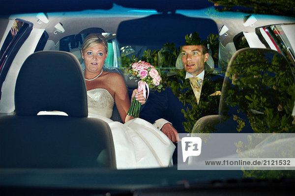 Brautpaar auf dem Rücksitz eines Autos