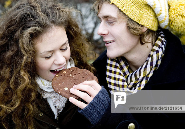 Young couple eating cookies