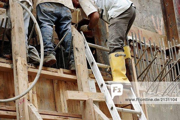 Bauarbeiter Gießen Wand hält Zement/Beton Schlauch