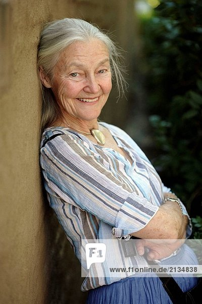 ältere Frau leaning on Wall und Lächeln in die Kamera