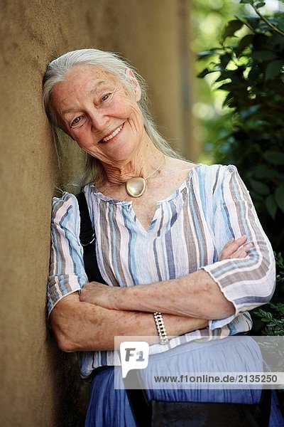 Senior woman leaning on wall and smiling in the camera