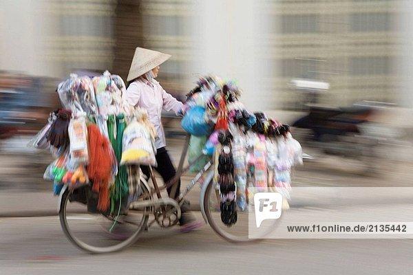 Frau Straßenhändler schieben ein Fahrrad  Hanoi  Vietnam