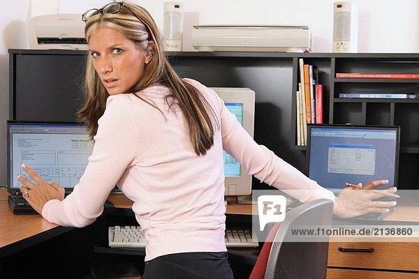 Frau in ihrer 20´s gefangen gestresst beschäftigt Arbeit an verschiedene Aufgaben auf mehreren Computern
