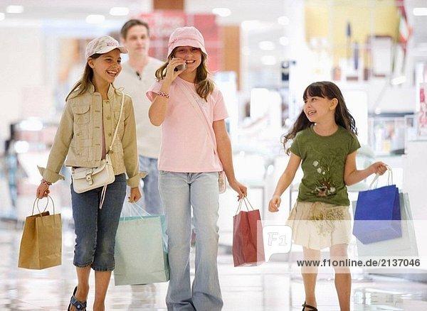 Caucasians  Hispanic  Alter von 9 und 10  shopping  am Telefon sprechen  lachen  Lächeln  Kaufhaus  Mall  junge Verbraucher