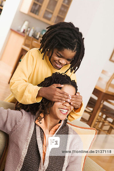 African American family at home  parents on sofa  son covering mother´s eyes with hands from behind. Guess who?