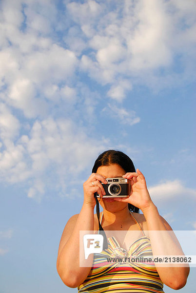 Latino Frau hält eine Kamera.
