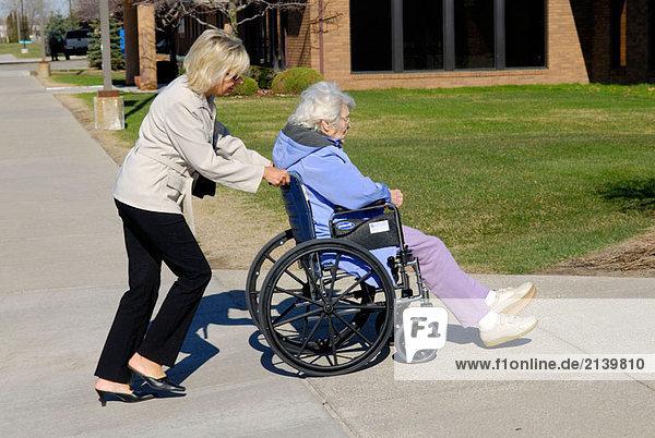 Erwachsene Tochter schiebt alternden Mutter an das Doktorbüro im Rollstuhl