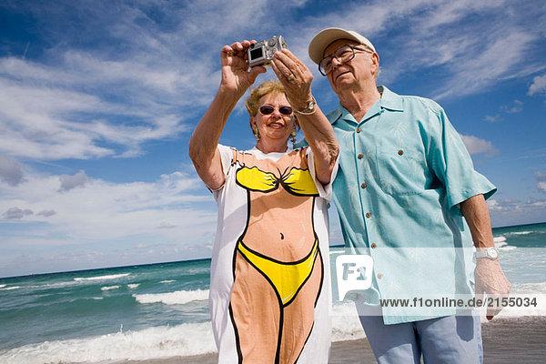 älteres Paar unter Fun Foto auf Strand.
