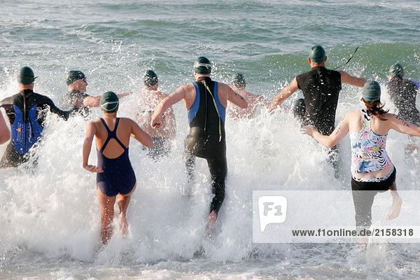 Mullet Man Triathlon  surf  swim  competitors  run  jump  splash. Gulf of Mexico Florabama. Alabama. USA.