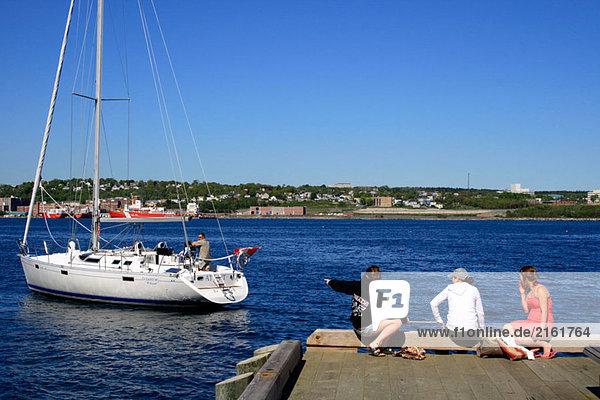 Harbour  Girls beobachten ein Segelboot. Halifax. Nova Scotia. Kanada.