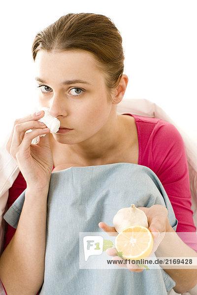 junge Frau hält Knoblauch und Zitrone