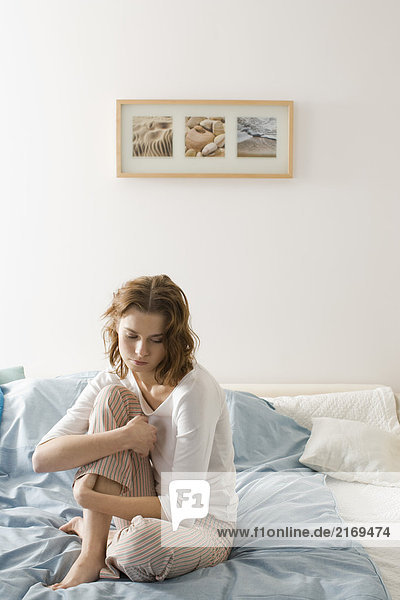 Young sad woman sitting on bed