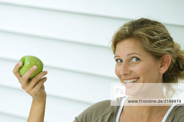 Frau hält Apfel hoch und lächelt in die Kamera
