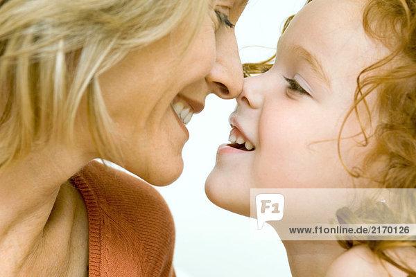 Mutter und Tochter berühren Nasen und lächeln sich an  Ausschnittansicht