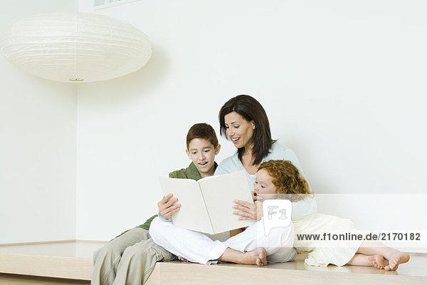 Mutter liest Buch für Junge und Mädchen