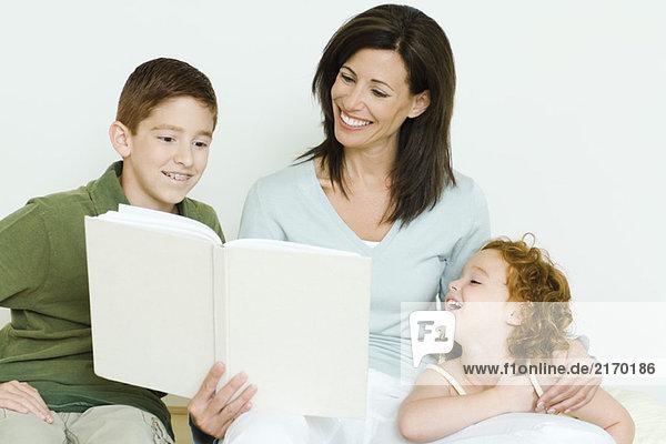Mutter liest Buch für Sohn und Tochter