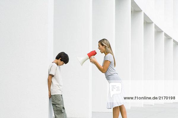 Frau schreit den Jungen durch das Megaphon an  der Junge senkt den Kopf.