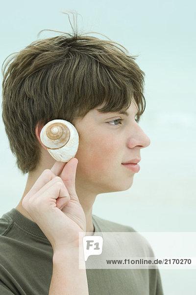 Teen boy holding up seashell to ear  profile