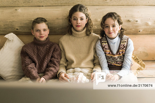 Three young siblings watching TV and eating marshmallows