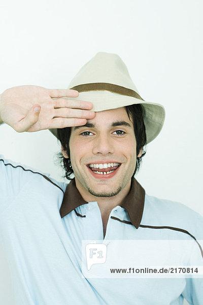 Junger Mann mit Hut  salutierend  lächelnd vor der Kamera