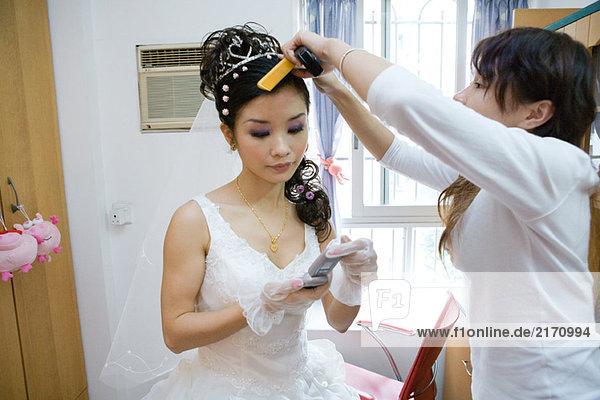 Braut  die ihr Haar von einem Freund gestylt bekommt und auf ihr Handy schaut.