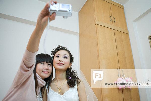 Frau hält Digitalkamera hoch  fotografiert sich selbst mit Braut
