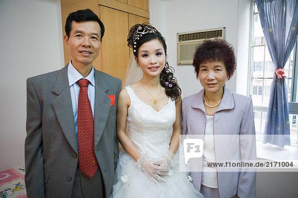 Braut steht zwischen den Eltern  lächelt in die Kamera  Porträt