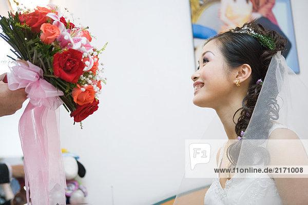 Braut wird mit Blumenstrauß überreicht  Schnittansicht