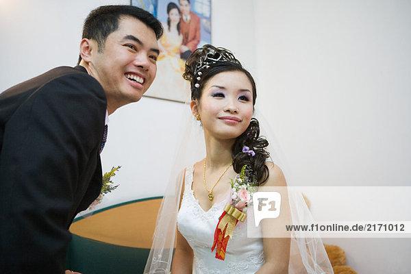 Braut und Bräutigam lächeln zusammen  schauen weg.