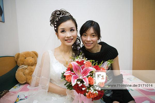 Braut im Bett sitzend mit Freundin  lächelnd  Portrait